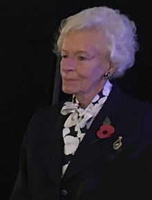 Photograph of Mary Ellis. An elderly woman with white hair wearing a dark blue suit and a red British Legion poppy.