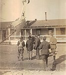 Men in front of a building where an aircraft with a black cat symbol has crashed into the roof. (24235791101).jpg