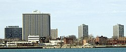 Several modernist gray high-rises with smaller, brown brick buildings beneath the bare trees among them, seen from across a body of water