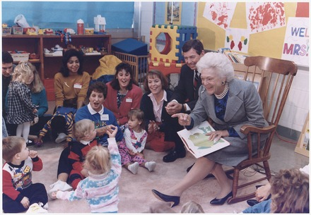"First Lady Barbara Bush, joined by Missouri Governor John Ashcroft, with a ""Parents as Teachers"" group at the Greater St. Louis Ferguson-Florissant School District in October 1991. Mrs. Bush, who championed literacy as first lady, is reading Brown Bear, Brown Bear to the children. Mrs. Bush and Missouri Governor John Ashcroft attend a ""Parents as Teachers"" parent-child group at the... - NARA - 186437.tif"