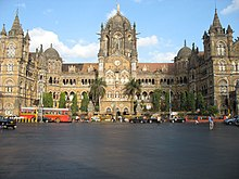 A brown building with clock towers, domes and pyramidal tops. Also a busiest railway station in India.[237] A wide street in front of it