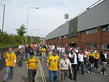 A group of people wearing predominantly yellow football shirts, walking along a road beside an association football stadium