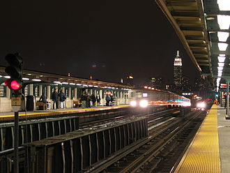 46th Street–Bliss Street (IRT Flushing Line) - Looking west at two Flushing-bound 7 trains approaching 46th Street-Bliss Street station at night