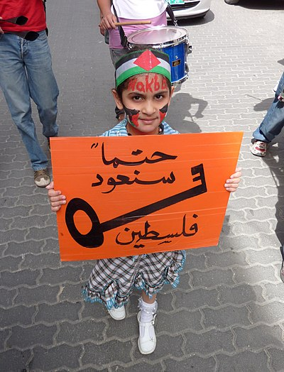 "Palestinian girl in a protest on Nakba Day 2010 in Hebron, West Bank. Her sign says ""Surely we will return, Palestine."" Most of the Palestinian refugees in the West Bank are descendants of people whose families hail from areas that were incorporated into Israel in 1948. The key is a symbol of the houses which Palestinians left as part of the Nakba. Nakba Day 2010 Hebron.JPG"