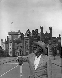 Black and white photograph of a man wearing a brimmed hat and blazer, standing in front of a stone castle-like building