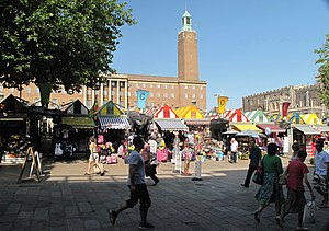 Row of brightly coloured market stalls. Behind the market stalls is a very large red brick building with a tall clock tower. Next to it is a long low dark stone building.