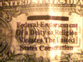 One dollar bill with In God We Trust marked out.jpg
