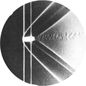 Shock wave - Schlieren photograph of the detached shock on a bullet in supersonic flight, published by Ernst Mach and Peter Salcher in 1887.