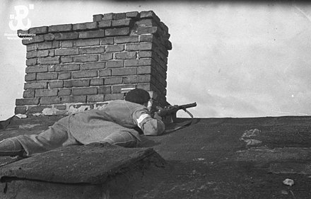 "Soldier from ""Piesc"" Battalion led by Stanislaw Jankowski ""Agaton"", pictured on a rooftop of a house near the Evangelic Cemetery in Wola District of Warsaw, 2 August 1944 Piesc-czujka.jpg"