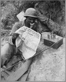 Private First Class Clarence Whitmore, voice radio operator, 24th Infantry Regiment, reads the latest news while... - NARA - 541945.tif