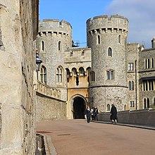 Uma fotografia de um portão de pedra, com duas grandes torres circulares de cada lado do portão dominando a imagem.  Uma parede de pedra se estende ao longo do lado esquerdo da imagem.