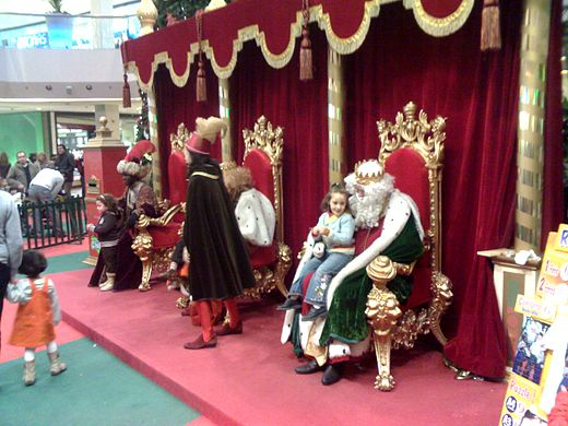 The Three Wise Men receiving children at a shopping centre in Spain. Letters with gift requests are left in the letterbox on the left-hand side. Reyes Magos en centro comercial.jpg
