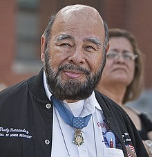Head and shoulders of a bald man with dark beard, with a medal hanging from a blue ribbon around his neck.