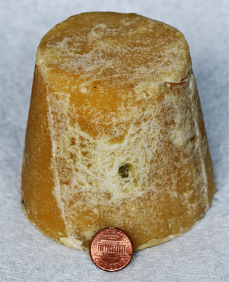 Jaggery - A block of jaggery, with a US penny for size comparison