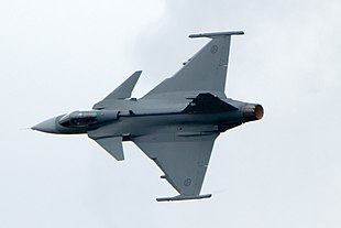 Grey fighter aircraft banking right, showing its top view, against a light-blue sky}}