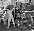 Sailors hauling out a torpedo from the stores of the depot ship HMS TYNE, to be loaded on to the destroyer HMS PENN, April 1942. A8443.jpg