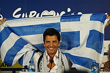 Smiling man, raising a blue-and-white Greek flag