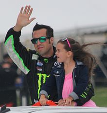 Hornish, in sunglasses, waves while holding his young daughter