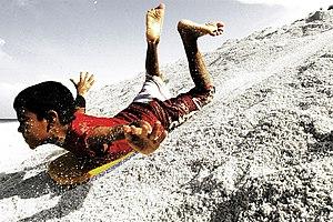 Sandboarding - A boy sandboarding in Fuvahmulah, Maldives