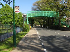 School House Corner - Pedestrian overbridge sited next to Ramsey Grammar School on the A3 Castletown to Ramsey road in Ramsey town with School House Corner beyond in the distance