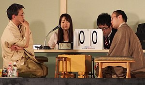 Professional shogi player -  professional shogi players, Yoshiharu Habu and Akira Watanabe, in 2014 with women's professional player Aya Fujita as timekeeper