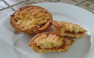 Hertzoggie - Two Jan Smuts Cookies, one of which has been broken in two to show the apricot jam filling.