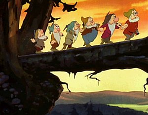 "Heigh-Ho - Six of the Seven Dwarfs (top center, right to left; Doc, Grumpy, Happy, Sleepy, Bashful, and Sneezy; Dopey cannot be seen) walking across a log, while singing the song, ""Heigh-Ho""."