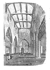 Interior of a church with a high vaulted ceiling, gallery balconies along the sides, and a large coat of arms on the chancel arch