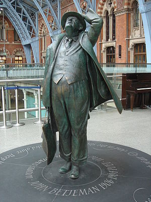 A large, bronze statue of a man. He is dressed in a suit, coat and hat and is looking up at the roof of a building.