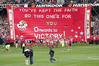 2005 AFL Grand Final - Image: Sydney break through their banner, 2005 AFL Grand Final
