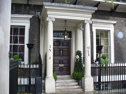 "Entrance of the Naval and Military Club in St James's Square, with ""IN"" and ""OUT"" in humorous reference to previous Cambridge House premises"