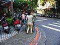 Two Foreign Care-Givers Pushing wheelchairs in Yanshou Street Sidewalk 20131201.jpg
