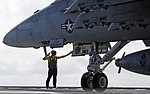 U.S. Navy Aviation Boatswain's Mate (Handling) 2nd Class Sylvester Williams directs an F-A-18E Super Hornet aircraft assigned to Strike Fighter Squadron (VFA) 105 on the flight deck of the aircraft carrier USS 130731-N-RA063-231.jpg