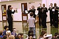 US Navy 060120-N-1194D-006 Chief Musician Roberta Haworth helps a young student direct the Seventh Fleet Band during a rousing concert for the children of Sasebo Elementary School.jpg