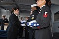 US Navy 061202-N-7312S-005 Chief Master-at-Arms Mary McQuain presents a folded flag to Master-at-Arms 1st Class Michael B. Thomas during a burial at sea for three military working dogs on board USS Blue Ridge (LCC 19).jpg