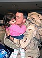 US Navy 080210-N-5292M-001 Lt. Robert O'Connell, assigned to Combined Joint Task Force-Horn of Africa (CJTF-HOA), kisses his daughter after returning to the Naval Air Terminal at Naval Station Norfolk.jpg