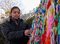 US Navy 080213-N-6326B-140 Operations Specialist 3rd Class Rae Reyes, assigned to the aircraft carrier USS Nimitz (CVN 68), admires a display of 1,000 origami paper cranes while touring the grounds of the Nagasaki Atomic Bomb M.jpg