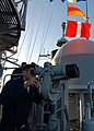 US Navy 080218-N-5476H-116 Quartermaster 3rd Class Ronald Masulis, of Danville, Ill., looks through ship mounted binoculars on the signal bridge in order to read flag signals from the guided-missile destroyer USS Decatur (DDG 7.jpg