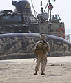 US Navy 100709-N-9500T-299 A Marine stands watch as a landing craft air cushion prepares to unload its cargo of Marines and vehicles onto the beach during an amphibious landing exercise.jpg