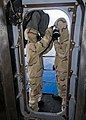 US Navy 100818-N-0754Y-071 Damage Controlman Fireman Courtney Fuller simulates decontaminating Aviation Structural Mechanic 2nd Class Nathan Hansen with an M-291 kit.jpg