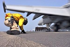 US Navy 110509-N-0569K-021 Lt. Mark D. Kurtz, an aircraft shooter, takes cover from jet blast as he launches an F-A-18F Super Hornet.jpg