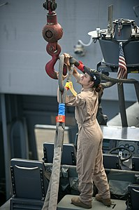 US Navy 110812-N-PB383-007 Engineman 3rd Class Miranda DaRae hooks a cable to a crane while unloading a rigid-hull inflatable boat before a practic.jpg