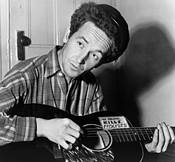 "Woody Guthrie with guitar labeled ""This Machine Kills Fascists"""
