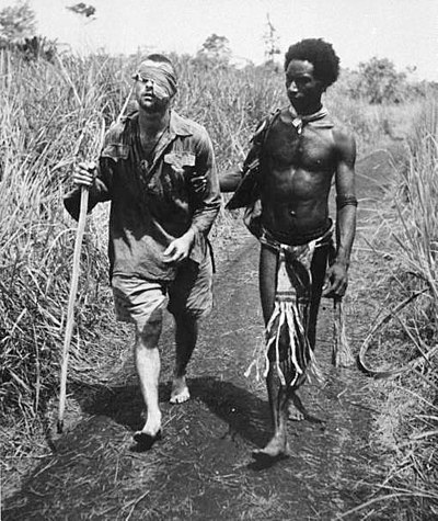 "An Australian soldier, Private George ""Dick"" Whittington, is aided by Papuan orderly Raphael Oimbari near Buna on 25 December 1942. Wounded Australian soldier led by a Papuan orderly at Buna.jpg"
