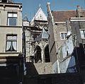 Zicht op het Paradijsportaal in het zuider transept, gezien tussen twee huizen door - Nijmegen - 20383617 - RCE.jpg