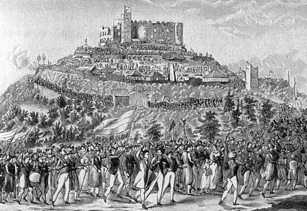 Pro-nationalist participants march to the ruins of Hambach Castle in 1832. Students and some professionals, and their spouses, predominated. They carried the flag of the underground Burschenschaft, which later became the basis of the flag of modern Germany.