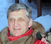 A man with grey hair, wearing a red and brown coat, with snow in the background.