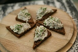 Five triangular slices of rye bread topped with vorschmack lying on a wooden place