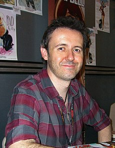 A man with brown hair in a grey and red checked shirt