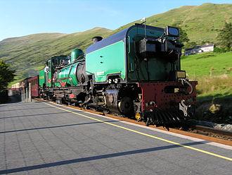 Welsh Highland Railway restoration - 138 'Mileniwm'/'Millennium' SAR NGG 16 Class Garratt arrives at Snowdon Ranger station with a southbound service from Caernarfon to Rhyd Ddu